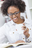 Afrikansk amerikankvinna som dricker kaffeläseboken Arkivfoton