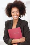 Afrikansk amerikankvinna som griper en röd mapp Royaltyfria Foton