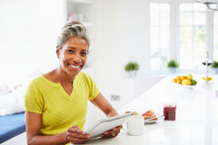 Afrikansk amerikankvinna som hemma använder den Digital minnestavlan Arkivfoto