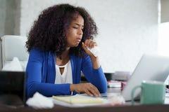 Afrikansk amerikankvinna som hemma arbetar att hosta och att nysa royaltyfri fotografi