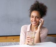 Afrikansk amerikankvinna som ler med mobiltelefonen Fotografering för Bildbyråer