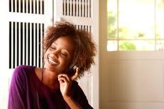 Afrikansk amerikankvinna som lyssnar till musik på hörlurar royaltyfria bilder