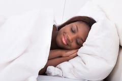 Afrikansk amerikankvinna som sover i säng Arkivfoton