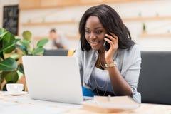 Afrikansk amerikankvinna som talar på smartphonen, medan genom att använda bärbara datorn i kafé royaltyfri foto