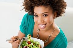 Afrikansk amerikankvinna som äter sallad Arkivfoto