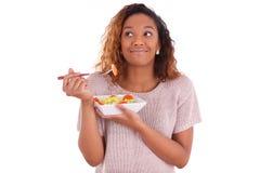 Afrikansk amerikankvinna som äter sallad som isoleras på vit backgroun Royaltyfri Bild