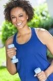 Afrikansk amerikankvinna som övar med vikter utanför Royaltyfri Bild