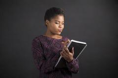 Afrikansk amerikankvinnahandstil i bokdagbok på svart tavlabakgrund royaltyfri fotografi