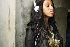 Afrikansk amerikankvinnan lyssnar till musik arkivbild