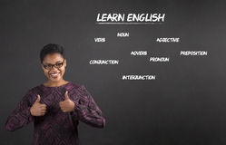 Afrikansk amerikankvinnan med tummar upp handsignal lär engelska på svart tavlabakgrund fotografering för bildbyråer