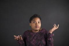 Afrikansk amerikankvinnan med vet jag inte gest på svart tavlabakgrund Royaltyfri Bild