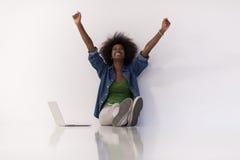 Afrikansk amerikankvinnasammanträde på golv med bärbara datorn royaltyfria bilder