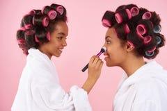 Afrikansk amerikanliten flicka som gör makeup med mamman royaltyfri fotografi