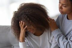 Afrikansk amerikanmammakram som tröstar den ledsna tonårs- dottern fotografering för bildbyråer