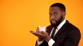 Afrikansk amerikanman i den formella dr?kten som rymmer piggybank, f?rtroendefull bank, besparingar royaltyfria bilder