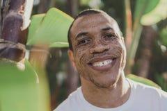 Afrikansk amerikanman med fräknar som ler utomhus Arkivfoto
