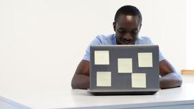 Afrikansk amerikanman som använder bärbara datorn arkivfilmer