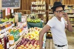 Afrikansk amerikanman som använder mobiltelefonen på supermarket royaltyfria foton