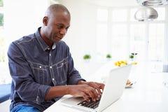 Afrikansk amerikanman som hemma använder bärbara datorn Fotografering för Bildbyråer