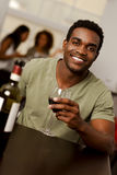 Afrikansk amerikanman som holiding ett vinexponeringsglas i en restaurang Arkivbild