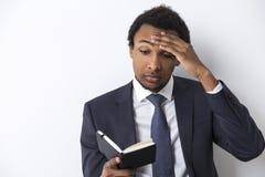 Afrikansk amerikanman som läser en svart anteckningsbok Arkivfoto