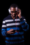 Afrikansk amerikanman som lyssnar till musik som isoleras på svart backgr arkivbild