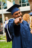 Afrikansk amerikanman som pekar på kameran på hans avläggande av examen Arkivfoton