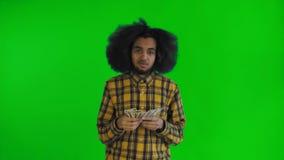 Afrikansk amerikanman som rymmer pengar i hans händer och tänker om något på den gröna skärmen eller nyckel- bakgrund för chroma stock video