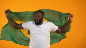 Afrikansk amerikanman som vinkar den brasilianska flaggan, stöttande nationellt sportlag arkivfilmer