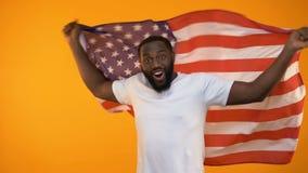 Afrikansk amerikanman som vinkar USA flaggan, stöttande nationellt sportlag, fan arkivfilmer
