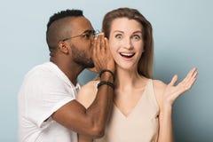 Afrikansk amerikanmannen ber?ttar hemligt till den chockade caucasian kvinnlign royaltyfri bild