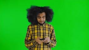 Afrikansk amerikanmannen med lockigt hår tänker för överför meddelandet på den gröna skärmen eller nyckel- bakgrund för chroma Be lager videofilmer