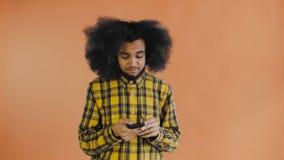 Afrikansk amerikanmannen med lockigt hår tänker för överför meddelandet på orange bakgrund Begrepp av sinnesr?relser arkivfilmer