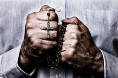 Afrikansk amerikanmannen räcker att be rymma en pärlradband med Jesus Christ i korset eller korset royaltyfria bilder