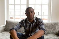 Afrikansk amerikanmannen sitter på soffan som gör den videopd appellen arkivbilder