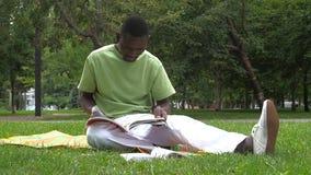 Afrikansk amerikanmannen skriver i en anteckningsbok på arkivfilmer