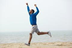 Afrikansk amerikanmanspring med händer lyftte på stranden Arkivfoton