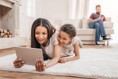 Afrikansk amerikanmoder och dotter som använder den digitala minnestavlan, medan ligga på matta hemma Royaltyfria Foton