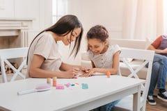 Afrikansk amerikanmoder och dotter som hemma gör manikyr Royaltyfria Foton