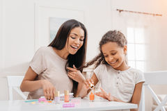 Afrikansk amerikanmoder som ser den lyckliga dottern som gör manikyr Arkivbild