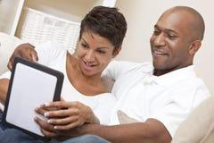 Afrikansk amerikanpar genom att använda Tabletdatoren royaltyfri foto
