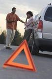 Afrikansk amerikanpar i diskussion över den brutna bilen Arkivfoton