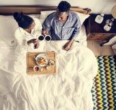 Afrikansk amerikanpar i säng som har en frukost i säng arkivbild