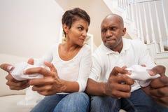 Afrikansk amerikanpar som har den roliga spela videopd konsolleken Arkivbild