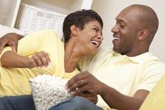 afrikansk amerikanpar äter filmpopcornwatchen Fotografering för Bildbyråer