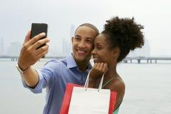 Afrikansk amerikanparshopping som tar Selfie med mobiltelefonen Arkivfoto