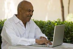 Afrikansk amerikanpensionär som arbetar på bärbar datordatoren Arkivfoto
