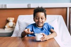 Afrikansk amerikanpojke som äter yoghurt arkivbilder