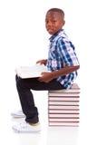 Afrikansk amerikanskolapojke som läser en bok - svarta människor arkivbild
