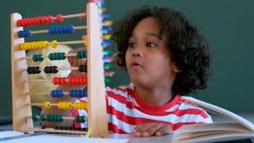 Afrikansk amerikanskolpojke som lär matematik med kulrammet på skrivbordet i ett klassrum stock video